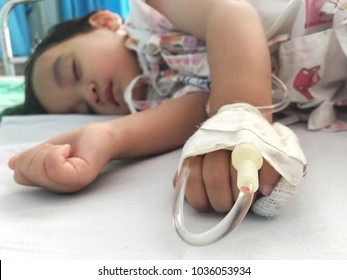 Baby boy sick and sleeping on patient bed at the hospital. Saline intravenous or (IV)drip in baby patient hand. Poor baby looks tired and exhausted.IV fluid replacement or correcting the dehydration.