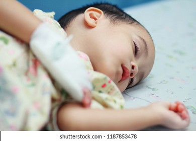 Baby boy sick and sleeping on patient bed at the hospital.Saline intravenous or (IV)drip in baby patient hand. Poor baby looks tired and exhausted.Rest on bed in the hospital with IV fluid replacement