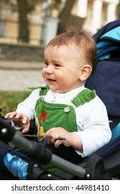 Baby boy sits in blue perambulator.