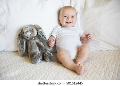 Baby boy sits on bed in a white onesie with toy bunny and smiles at camera