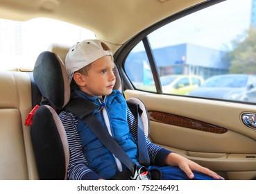 Baby boy sitting in child car seat in car. Preschool age boy in a booster seat