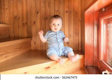 Baby boy sitting and climbing up stairs.