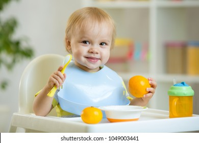 Baby boy sitting in highchair and eating oranges
