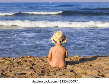 Baby boy sitting on the beach near the water.