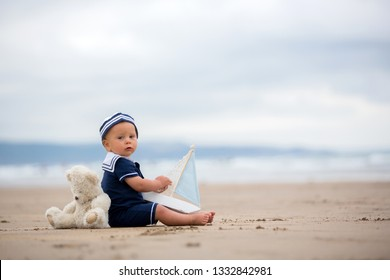 Baby boy sitting on the beach near the water and plays with a toy ship and teddy bear