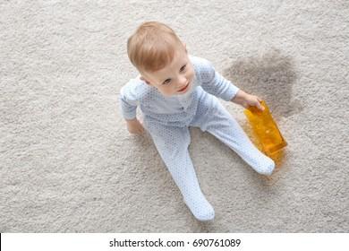 Baby boy sitting on carpet with empty glass near wet spot