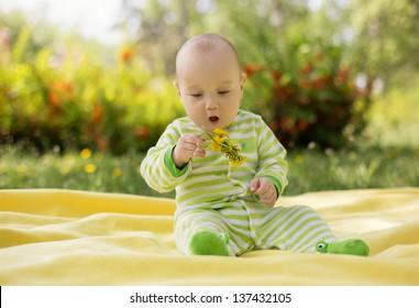 baby boy sitting on grass in spring flowery garden