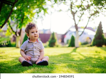 baby boy sitting on the grass in the yard