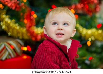 A baby boy is sitting on the living room floor next to a decorated Christmas tree and wrapped presents. He looks up and smiles and laughs.