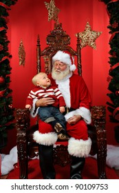 Baby boy sitting on Santa's lap at Christmas time.
