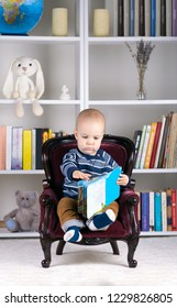 Baby boy sitting on a small chair and reading his book in front of a library