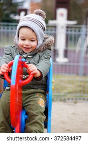 Baby boy sitting in a spring swing on a play ground