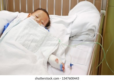 Baby boy sleeping with attaching intravenous tube to hand on bed at hospital. Baby admitted at hospital. Kid patients have IV tube.