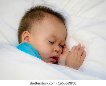 A baby boy is sleeping in the bed