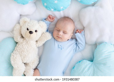 baby boy sleeping on the bed lying on his back with a soft teddy bear among the pillows in blue pajamas, healthy newborn sleep