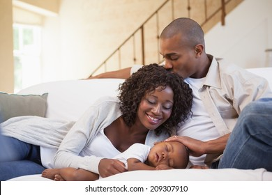 Baby boy sleeping peacefully on couch with happy parents at home in the living room
