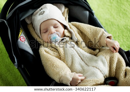Baby Boy Sleeping In A Safety Infant Car Seat Carrier