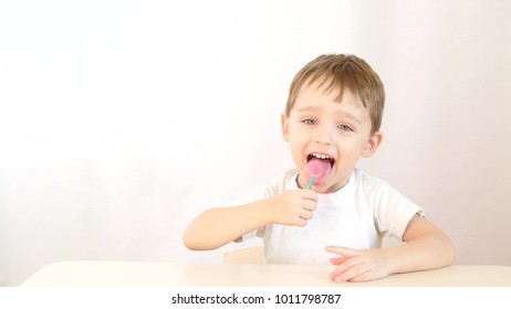 Baby boy smiling and eating lollipops on a stick, sitting at a table on a white background.