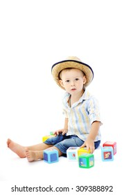 baby boy in a straw hat playing with multicolored cubes on a white background