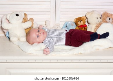 Baby boy in striped bodysuit and dark red trousers. Infant with blue eyes and peaceful face among teddy bears on wooden background. Baby lying on white duvet. Childhood and innocence concept