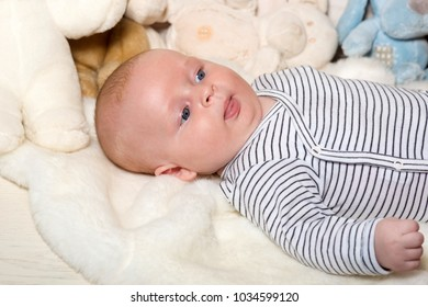 Baby boy in striped bodysuit. Baby lying on white duvet, close up. Infant with blue eyes and interested face on light blanket with soft toys on background. Childhood and innocence concept