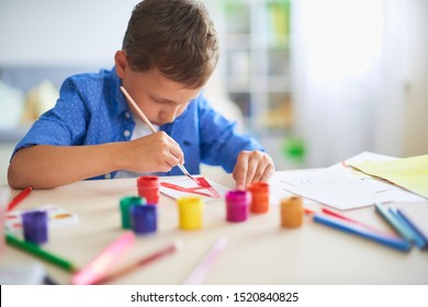 baby boy studying at home.happy child at the table with school supplies smiles and learns the alphabet in a playful way.happy student in bright room draws the letters with brush and paints in gouache