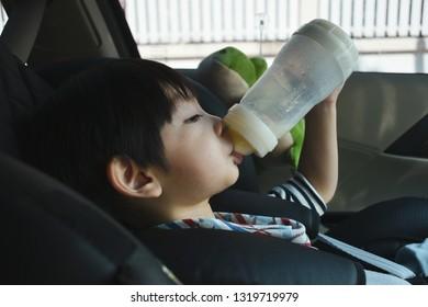 baby boy sucking milk on car seat safety drive