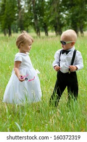 baby boy in sunglasses looks at baby girl (both are dressed as bride and groom)