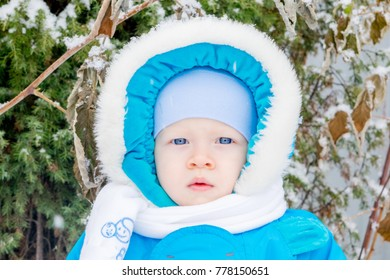 Baby boy surprised with first snow holding snow at his hand