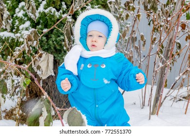 Baby boy surprised with a snow at a winter garden