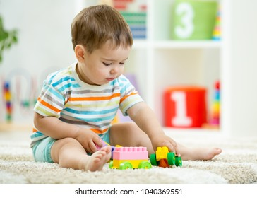 Baby boy toddler playing wooden toys at home