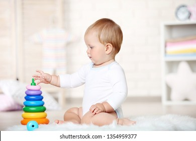 Baby boy with toys sitting on carpet at home