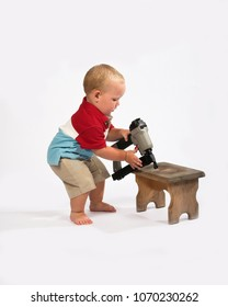 Baby boy trying to use a nail gun on a wooded stool (insolated)