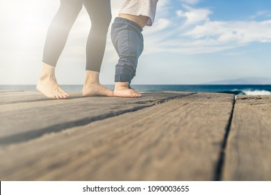 Baby boy walking on the beach in beautiful summer day. Mother with toddler son learning to walk on wooden beach sidewalk.
