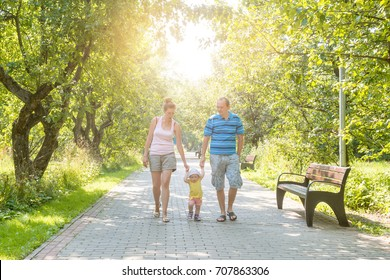 A baby boy walks by the handle with mom and dad in the park. The sun is shining