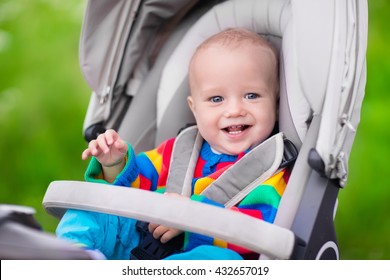 Baby boy in warm colorful knitted jacket sitting in modern stroller on a walk in a park. Child in buggy. Little kid in a pushchair. Traveling with young kids. Transportation for family with infant.