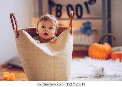 Baby boy wear costume and playing on floor on Halloween, he is hiding and peeking from bag