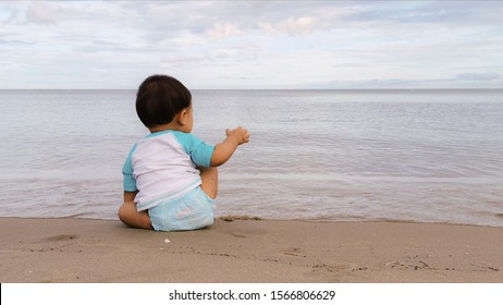The baby boy wear white swimming shirt with blue sleeves and swim diaper pants sit back on the beach with the sea and the sky are background.