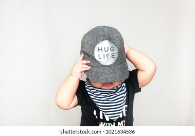 A baby boy is wearing a boy's cap with a message