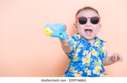 Baby Boy wearing flower shirt smiled happily to welcome Songkran festival with water gun on hand with copy space for your text