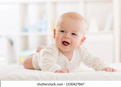 Baby boy wearing white clothes in sunny nursery room. Newborn child relaxing in bed.
