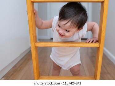 Baby boy in white jumpsuit play peek a boo at the wooden ladder