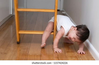 Baby boy in white jumpsuit stuck at the wooden ladder while trying to climb over. Baby is crying when failed from the ladder