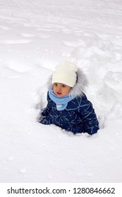 baby boy in the winter in blue overalls on the street in the Park with snow
