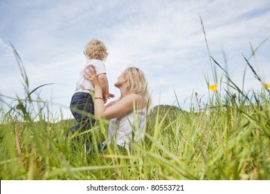 Baby boy and young mother looking at a view