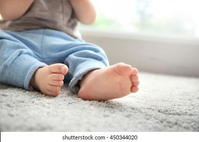 Baby boy's feet on woolen carpet, close up
