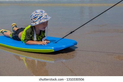Baby boy's having fun skimming on bodyboard
