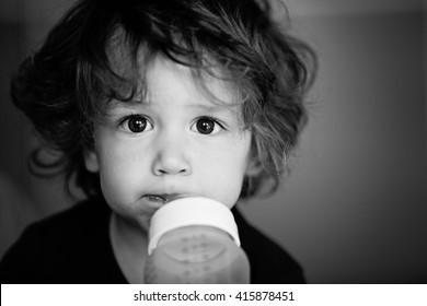 Baby boy/toddler, sucking a bottle of milk. Shallow DOF Black and White