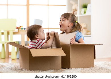 Baby brother and child sister playing in cardboard boxes in nursery