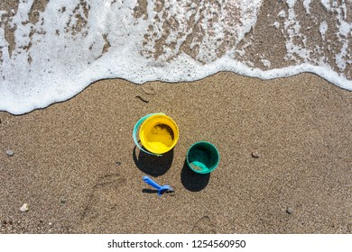 Baby bucket and shovel stand on the sand on the beach near the water on a sunny day. View from above
